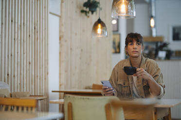 Female owner looking away while holding coffee cup using smart phone sitting in cafe - GUSF04612