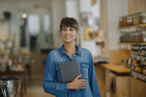 Happy female owner holding digital tablet looking away while standing in coffee shop - GUSF04621