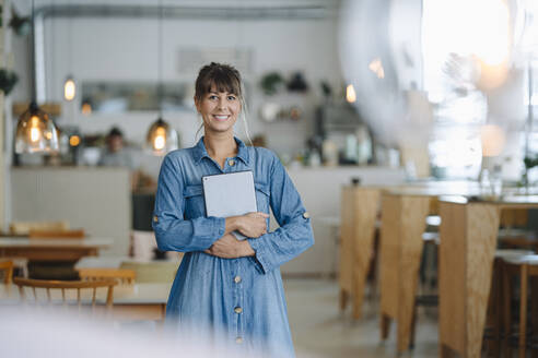 Happy female entrepreneur using digital tablet while standing in coffee shop - GUSF04624