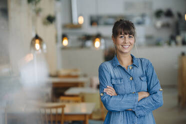 Smiling female owner with arms crossed standing in coffee shop - GUSF04627