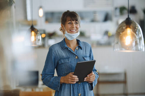 Female entrepreneur wearing protective face mask looking away using digital tablet while standing in cafe - GUSF04645