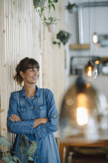 Smiling female entrepreneur looking away with arms crossed by wooden wall - GUSF04654