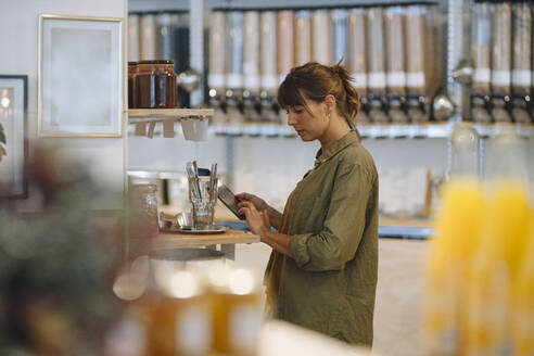 Female entrepreneur using digital tablet while standing coffee shop - GUSF04672