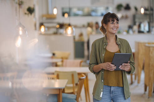 Smiling female entrepreneur looking away while holding digital tablet standing in cafe - GUSF04678