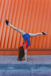 Young woman doing handstand against orange wall - MGRF00013