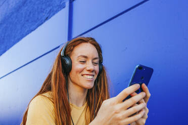Redhead woman wearing headphones using mobile phone while sitting against blue wall - MGRF00016