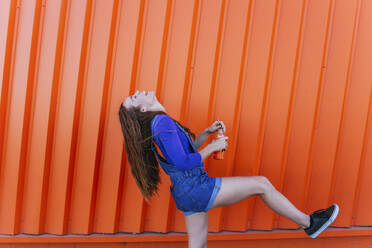 Cheerful woman drinking juice while standing against orange wall - MGRF00022