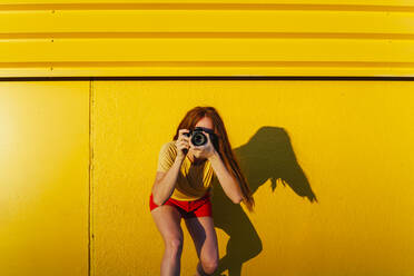 Woman photographing through camera while standing against yellow wall - MGRF00028