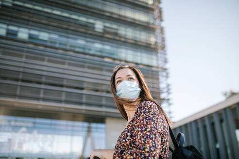 Woman in protective face mask against building in city during COVID-19 - GRCF00432