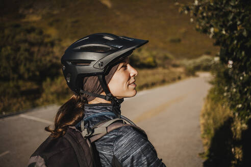 Woman wearing cycling helmet standing on mountain path at Somiedo Natural Park, Spain - DMGF00243