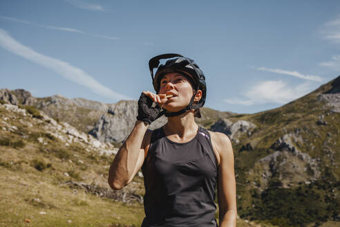 Woman wearing cycling helmet eating biscuit while standing against mountain at Somiedo Natural park, Spain - DMGF00264