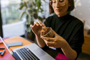 Businesswoman holding cake while sitting by laptop at home - VABF03811
