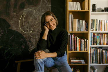 Smiling woman with hand in hair sitting against bookshelf at home - VABF03826