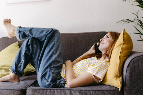 Young woman talking on smart phone while lying on sofa at home - TCEF01274