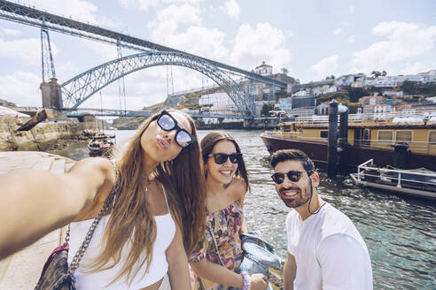 Cheerful young friends taking selfie against Douro River in city, Porto, Portugal - RSGF00390