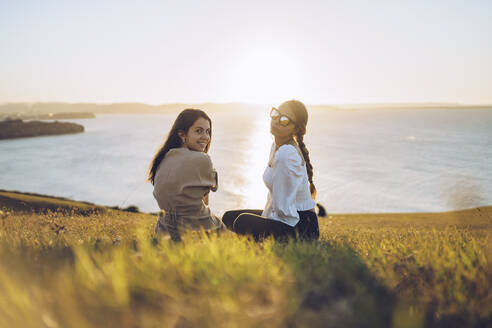 Young female friends sitting on hill at Mirador de La Providencia, Gijon, Spain - RSGF00408
