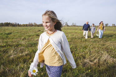 Smiling girl walking on field while family in background - EYAF01388