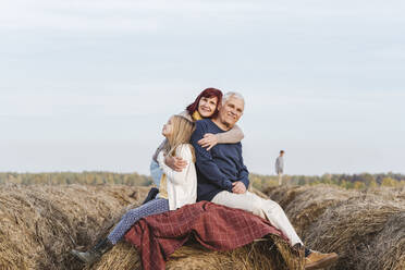 Granddaughter with grandparents on hay bale against sky during weekend - EYAF01397