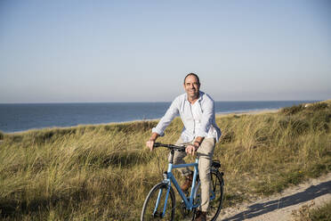 Smiling mature man riding bicycle at beach against clear sky - UUF21978