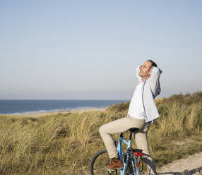Mature man on bicycle with hands behind head at beach against clear sky - UUF21981