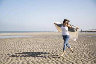 Carefree young woman running while holding blanket at beach against clear sky - UUF22032