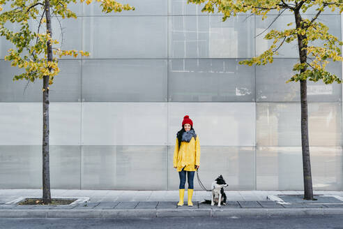 Smiling woman standing with dog on footpath during autumn - EBBF01195