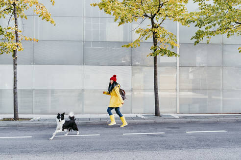 Happy woman running on street behind dog during autumn - EBBF01207