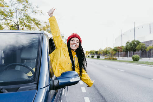 Carefree woman with arms outstretched leaning out of car - EBBF01243