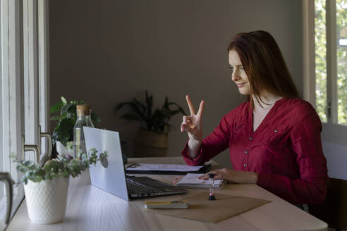 Doctor showing peace sign to video call on laptop while sitting at home - AFVF07450