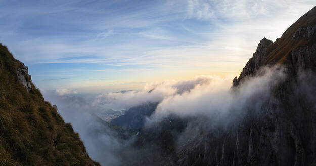 Idyllic shot of mountain covered by clouds during sunrise at Bergamasque Alps, Italy - MCVF00643