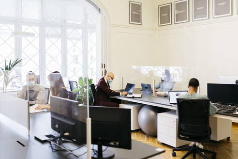Business professionals with protective mask working at desk in office - JRFF04806