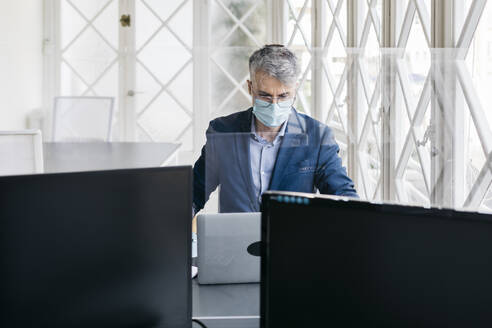 Male entrepreneur with protective mask working on laptop in office seen through glass division - JRFF04812