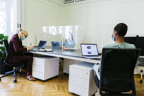 Business professionals with protective mask working at desk in office - JRFF04890