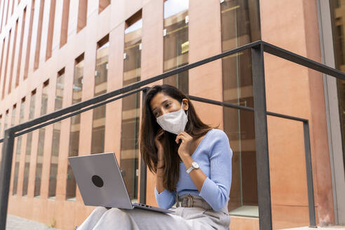Businesswoman wearing protective face mask while using laptop outside office building during COVID-19 - AFVF07489