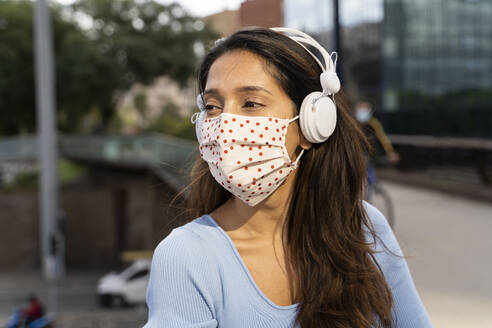 Young businesswoman in protective face mask listening music through headphones - AFVF07513