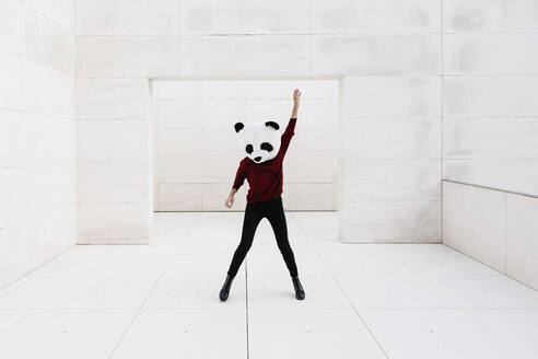 Woman wearing panda mask with hand raised while standing against doorway - XLGF00761