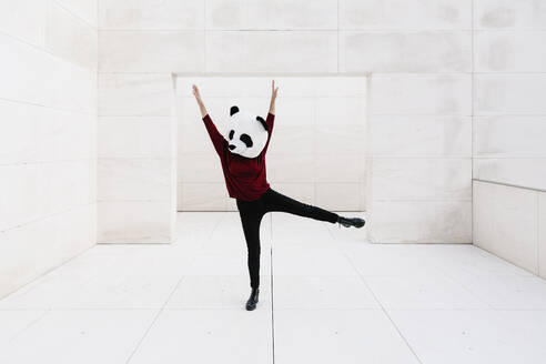 Woman wearing panda mask with arms raised standing against doorway - XLGF00764