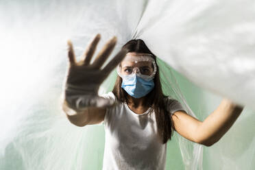 Young woman wearing protective face mask doing stop gesture while covered in plastic during COVID-19 - GIOF09523