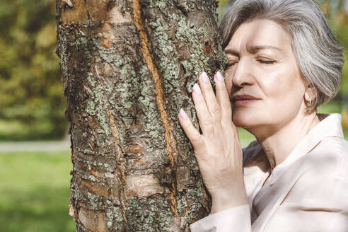 Woman with eyes closed embracing tree while standing at park - VYF00244