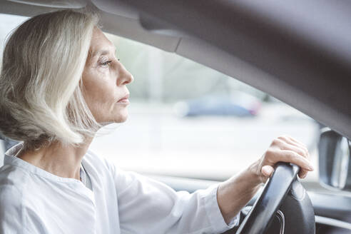 Mature businesswoman with short white hair driving car in city - VYF00274