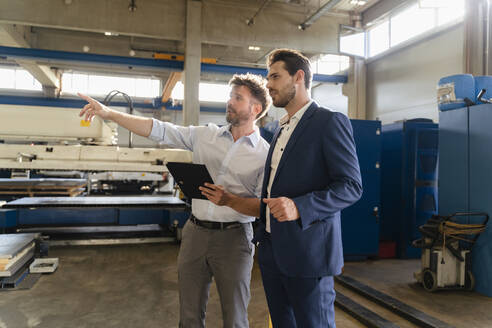 Businessman holding digital tablet working while standing by businessman at factory - DIGF13057