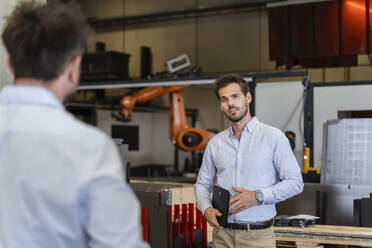 Young businessman talking with colleague while standing at factory - DIGF13075