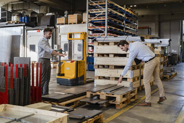 Business people inspecting metal material while standing at warehouse in factory - DIGF13078