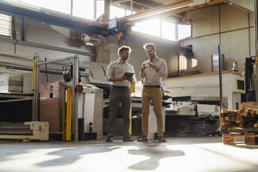 Businessman with digital tablet standing by colleague checking metal object at factory - DIGF13081