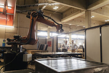 Business people looking automated robotic arm while standing at factory - DIGF13090