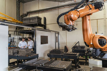 Automated robotic arm machine with business people standing in background at factory - DIGF13093