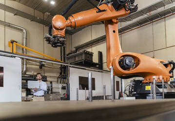 Young businessman with laptop examining automatic robot arm machine at factory - DIGF13099
