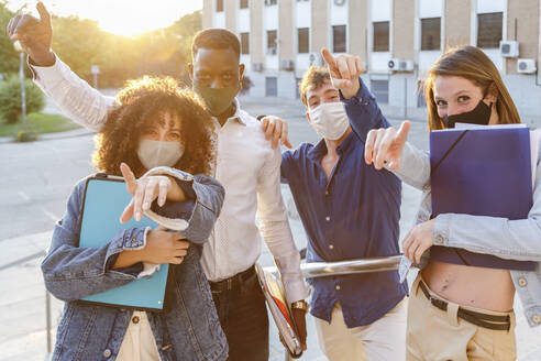 University students wearing protective face mask while pointing against education building - IFRF00053