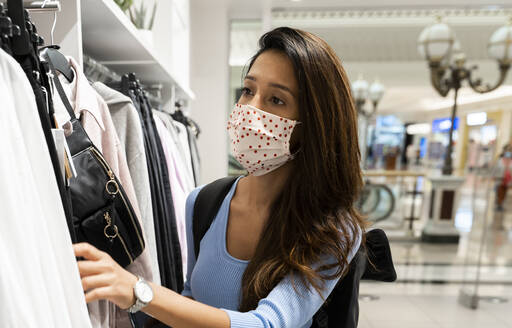 Woman wearing protective face mask while looking at clothes in shopping mall - AFVF07542