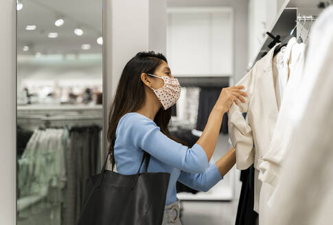 Woman wearing protective face mask while looking at suits in shopping mall - AFVF07545